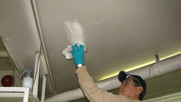 Employee cleaning ceiling in Nanaimo